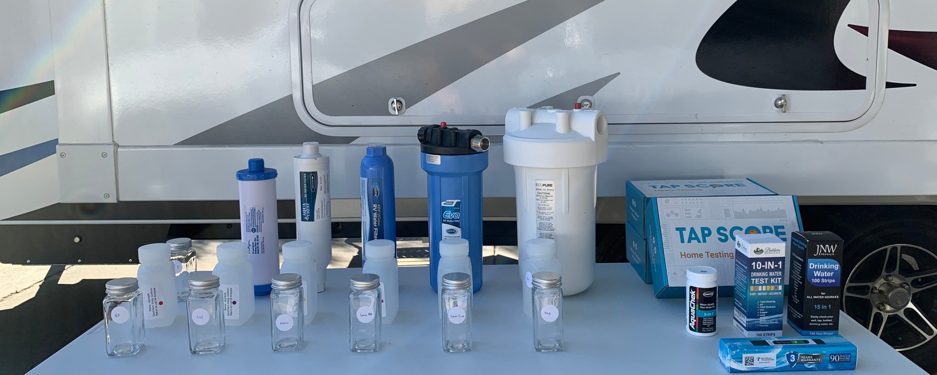 Image of the Culligan RV-8001 Water Filter, AquaCrest RV Inline Water Filter, and Camco TastePURE RV/Marine Water Filter, along with water quality test kits and the Tap Score commercial water quality testing kit.